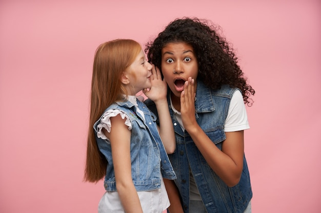 Portrait intérieur de jeunes filles portant un look de famille tout en posant sur le rose, en gardant les mains près de leur visage tout en partageant des nouvelles surprenantes