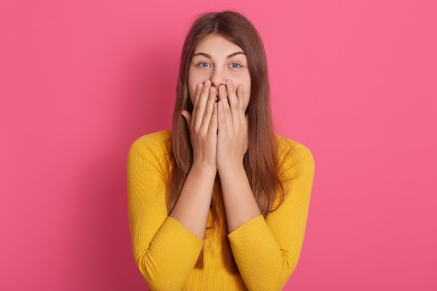 Portrait intérieur d'un joli mannequin choqué portant un sweat-shirt jaune, couvrant la bouche avec les mains, étant surpris, ayant les cheveux longs blonds, étant charismatique. concept d'émotions.