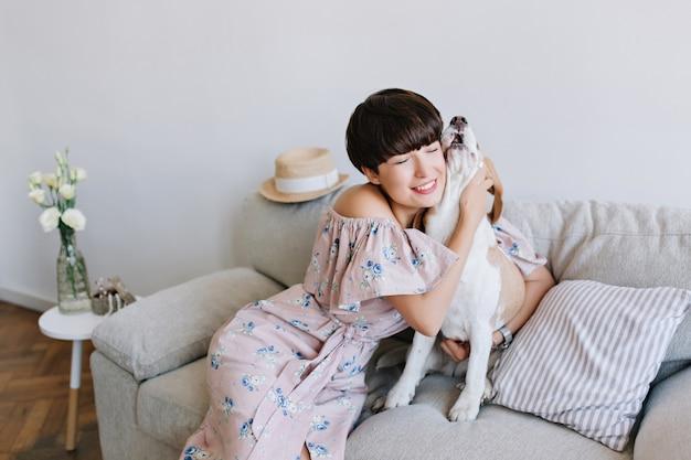 Portrait intérieur de jolie jeune femme aux cheveux courts embrassant son animal de compagnie sur le canapé