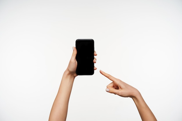 Portrait intérieur de la jolie jeune femme mains tenant le téléphone mobile et montrant sur écran noir avec l'index, étant isolé sur blanc