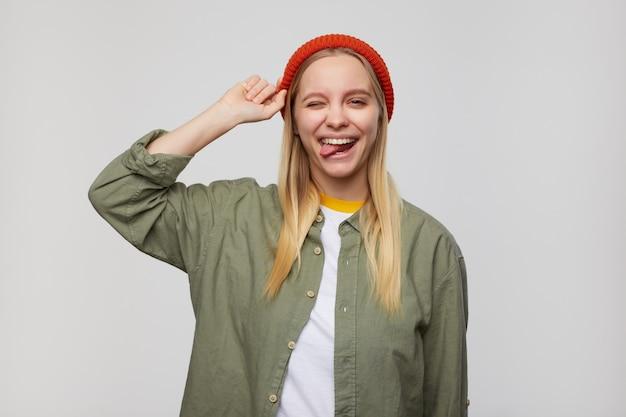 Portrait intérieur de joyeuse jeune femme à tête blanche avec un maquillage naturel clignotant joyeusement et montrant la langue, debout sur le bleu