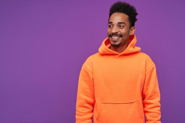Portrait intérieur de joyeux jeune homme brune assez barbu avec une peau foncée à côté avec un sourire charmant, être de bonne humeur tout en posant sur violet