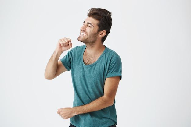 Portrait intérieur d'un mec espagnol expressif avec une coupe de cheveux élégante en t-shirt bleu, souriant, chantant, ouvrant largement la bouche et portant les yeux. le langage du corps