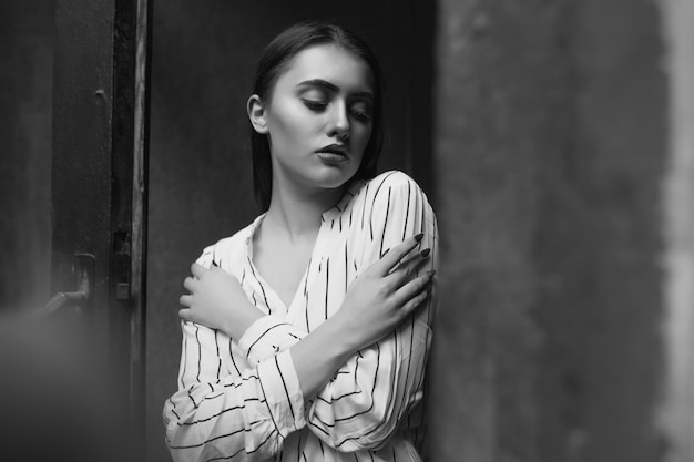 Le portrait d'intérieur noir et blanc d'une jeune femme sensuelle triste porte une chemise blanche rayée