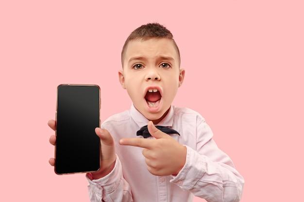 Portrait intérieur de séduisant jeune garçon tenant un smartphone vierge