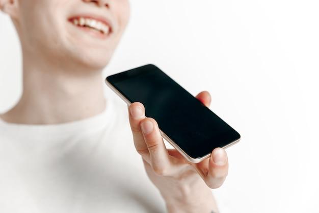 Portrait intérieur de séduisant jeune homme tenant un smartphone