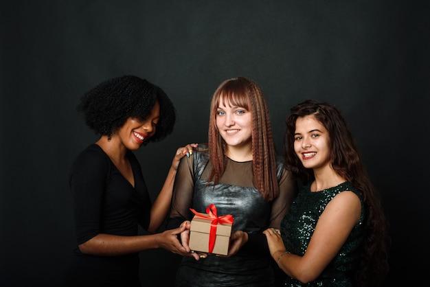 Portrait intérieur de trois sœurs bestfriends heureux femmes tenant des cadeaux et des cadeaux lumineux