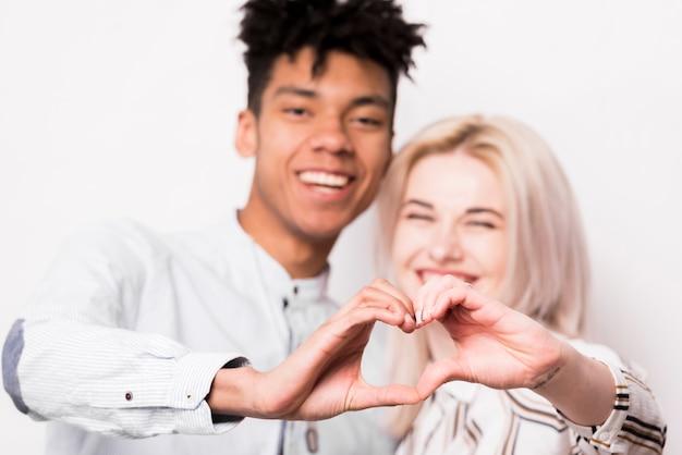 Portrait, de, interracial, couple, sourire, forme coeur, à, leurs, mains