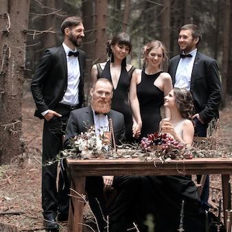 Portrait d'un invité et d'un couple de jeunes mariés près d'une table de pique-nique dans les bois