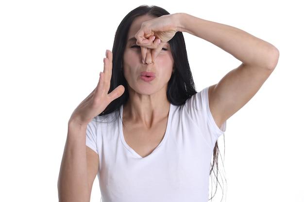 Portrait irrité d'une jeune femme couvrant le nez de la mauvaise odeur. odeurs désagréables dans le concept de la maison