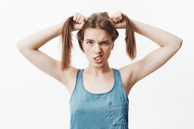 Portrait isolé de drôle jeune femme caucasienne aux cheveux noirs en chemise bleu vif, tenant les cheveux avec les mains, avec une expression de visage idiot, montrant les dents.