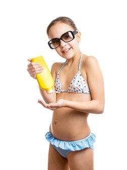 Portrait isolé d'une fille heureuse appliquant une lotion solaire