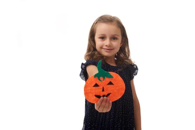 Portrait isolé sur fond blanc avec espace de copie d'une belle petite fille, jolie enfant de 4 ans, tenant une citrouille coupée en feutre maison, symbole de la fête d'halloween, et la montrant à la caméra