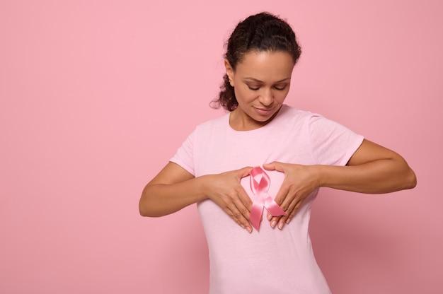 Portrait isolé sur fond coloré d'une femme afro-américaine en t-shirt rose, mettant ses mains sur sa poitrine en forme de coeur avec un ruban de satin rose au centre. journée mondiale de sensibilisation au cancer.