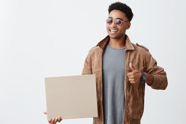 Portrait isolé de jeune étudiant africain à la peau sombre avec des cheveux bouclés dans une tenue à la mode décontractée et des lunettes de soleil tenant un carton, montrant le pouce vers le haut, sourit vivement. émotions positives