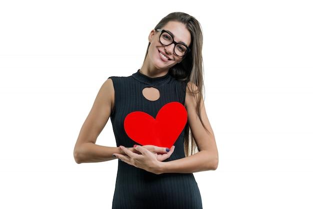 Portrait isolé de jeune femme avec coeur de papier rouge