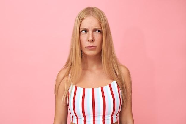 Portrait isolé de jeune femme sérieuse réfléchie avec de longs cheveux blonds regardant avec une expression faciale incertaine