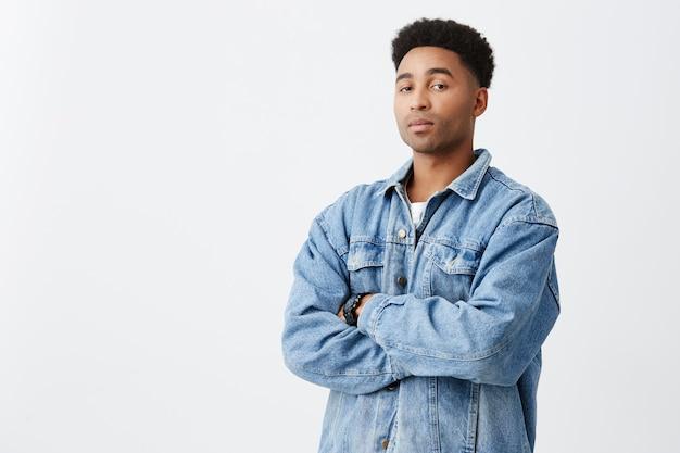 Portrait isolé de jeune homme à la peau sombre drôle avec les bras croisés avec une coiffure afro en chemise blanche décontractée sous une veste en jean avec une expression de visage concerné