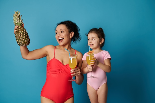 Portrait isolé d'une jolie fille et femme en maillot de bain avec un verre de jus dans ses mains et en regardant un délicieux ananas dans la main de sa mère.