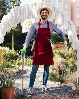 Portrait, jardinier, debout, houe, panier, mains