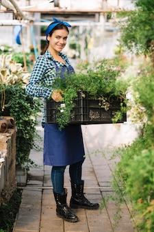Portrait d'un jardinier femme souriante tenant la caisse avec des plantes fraîches