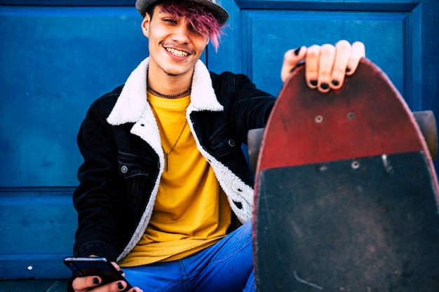 Portrait d'un jeune adolescent alternatif heureux et joyeux avec une planche à roulettes et un téléphone portable