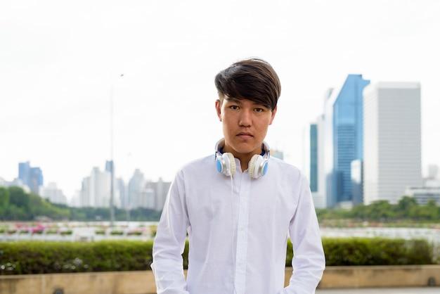 Portrait de jeune adolescent asiatique portant des écouteurs tout en vous relaxant dans le parc de bangkok, thaïlande