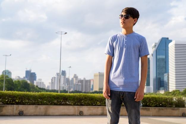 Portrait de jeune adolescent asiatique portant des lunettes de soleil tout en vous relaxant dans le parc de bangkok, thaïlande