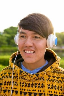 Portrait de jeune adolescent asiatique portant un sweat à capuche et un casque tout en vous relaxant dans le parc de bangkok, thaïlande