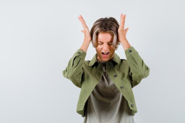 Portrait d'un jeune adolescent gardant les mains sur la tête tout en criant en t-shirt, en veste et en regardant la vue de face irritée
