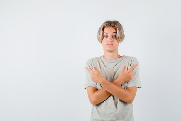 Portrait de jeune adolescent pointant à droite et à gauche en t-shirt et à la vue de face indécise