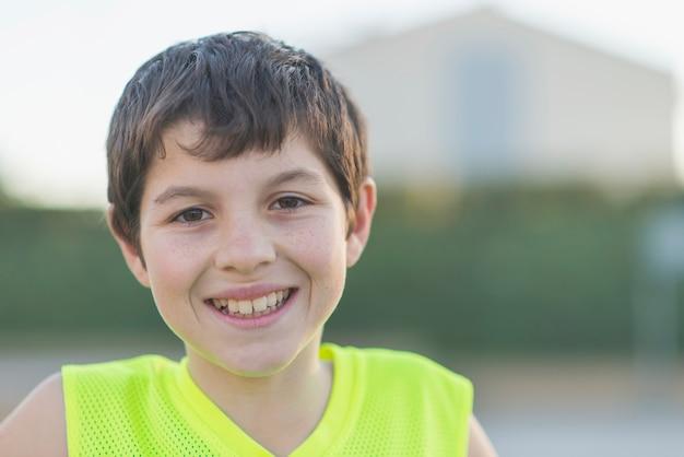 Portrait, jeune, adolescent, porter, jaune, basket-ball, sans manche, sourire