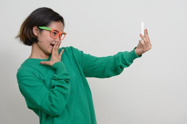 Portrait de jeune adolescente asiatique aux cheveux courts contre le mur blanc