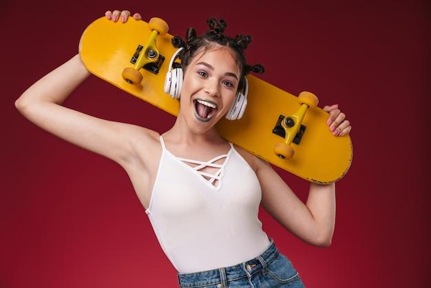 Portrait d'une jeune adolescente punk émotionnelle positive écoutant de la musique avec des écouteurs isolés sur un mur rouge bordeaux tenant une planche à roulettes