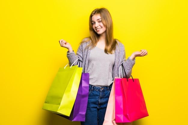 Portrait de jeune adolescente souriante heureuse avec des sacs à provisions, isolé