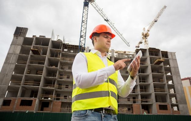 Portrait de jeune architecte en casque et gilet de sécurité à l'aide d'une tablette numérique