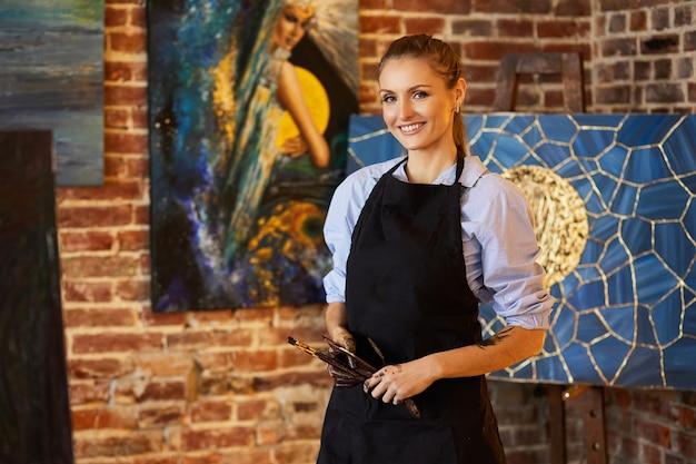 Portrait de jeune artiste féminine souriante portant un tablier dans un studio d'art. peintre tenant des pinceaux d'art, les mains sont tachées de peinture. processus créatif, détente, loisirs, passe-temps, gestion du stress.