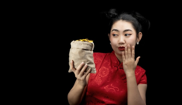 Portrait jeune asiatique, femme robe rouge cheongsam traditionnel tenant une pièce d'or dans un sac à l'arrière-plan noir