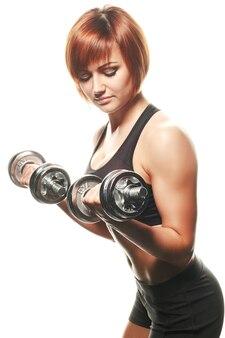 Portrait de jeune athlète féminine faisant des boucles d'haltères. studio tourné, isolé, fond blanc