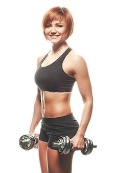 Portrait de jeune athlète rousse regardant et souriant à la caméra tout en tenant des haltères.fond blanc, isolé, tourné en studio