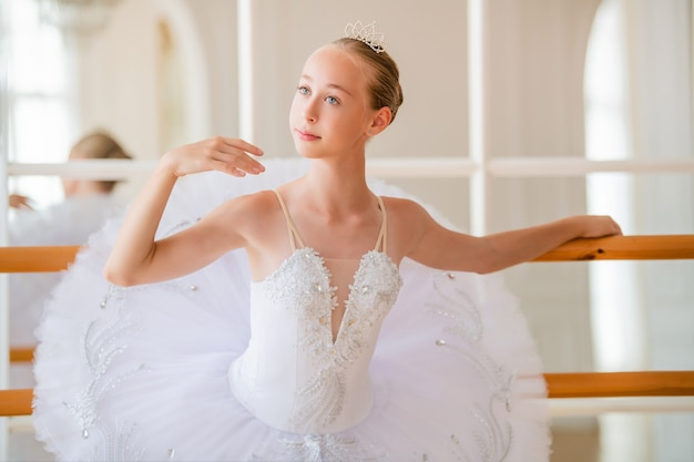 Portrait d'une jeune ballerine dans un beau tutu blanc près de la barre de ballet dans une grande belle salle blanche.