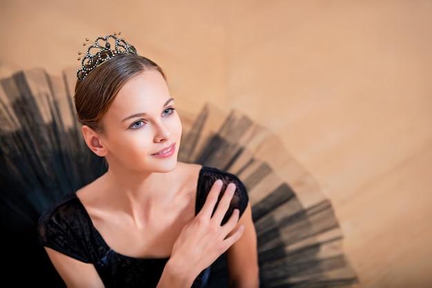 Portrait d'une jeune ballerine dans un tutu noir et une couronne