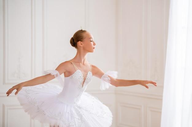 Portrait d'une jeune ballerine élancée dans un tutu blanc dans une pose élégante dans une grande et belle salle blanche.