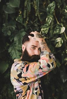 Portrait, jeune, barbu, tatouage, main