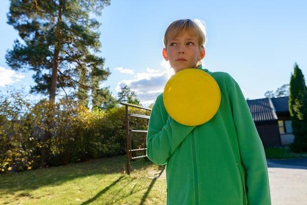 Portrait de jeune beau garçon aux cheveux blonds dans la cour avant à la maison