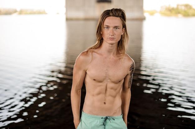 Portrait, jeune, beau, long, roux, homme, habillé, short, debout, dans, eau