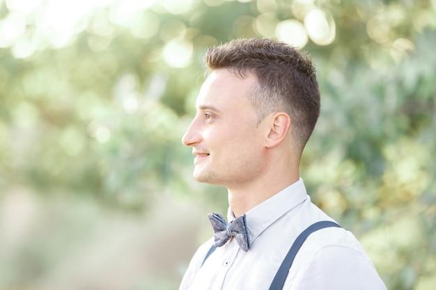Portrait d'un jeune beau marié à l'extérieur au coucher du soleil. photographie d'art