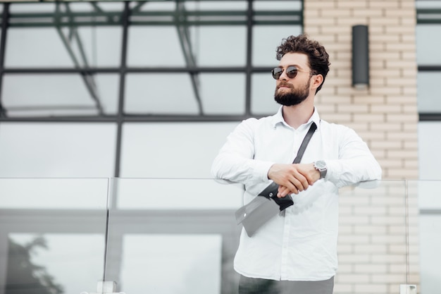 Portrait d'un jeune beau mec élégant dans une chemise blanche dans les rues de la ville en lunettes de soleil