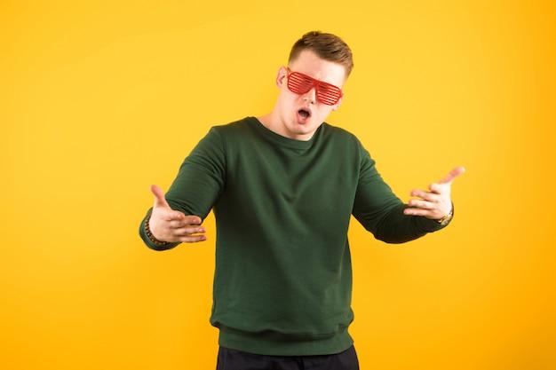 Portrait de jeune beau mec souriant avec des lunettes de soleil montrant le geste à bras ouverts
