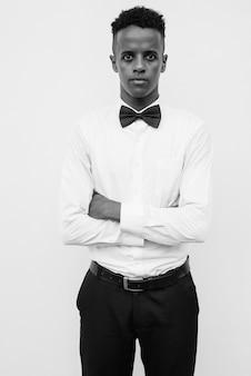 Portrait de jeune bel homme d'affaires africain avec noeud papillon contre un mur blanc en noir et blanc